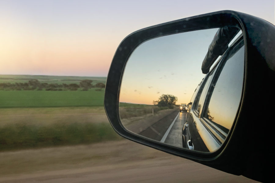 View of the side mirror as a car drives past a grassy field at sunset