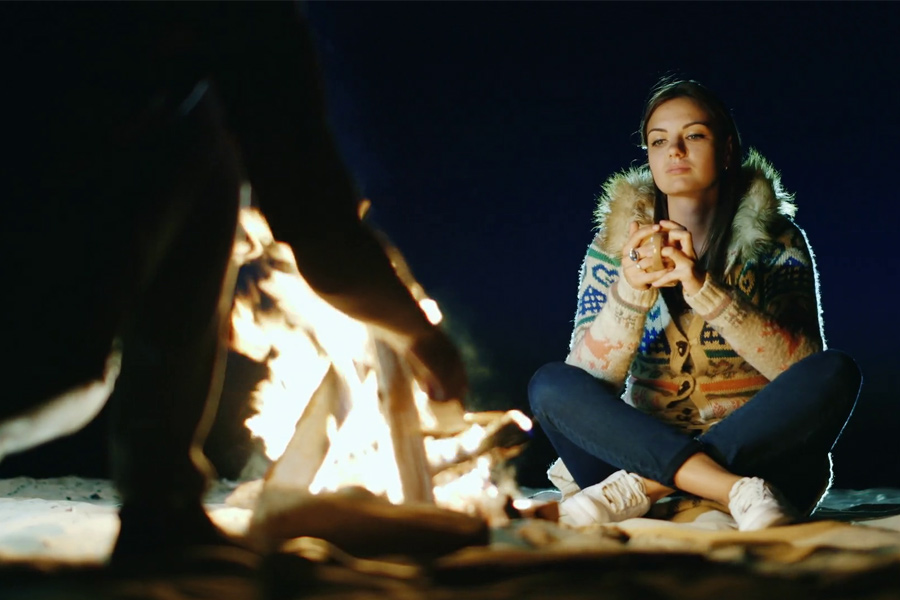 Woman-keeping-warm-by-campfire
