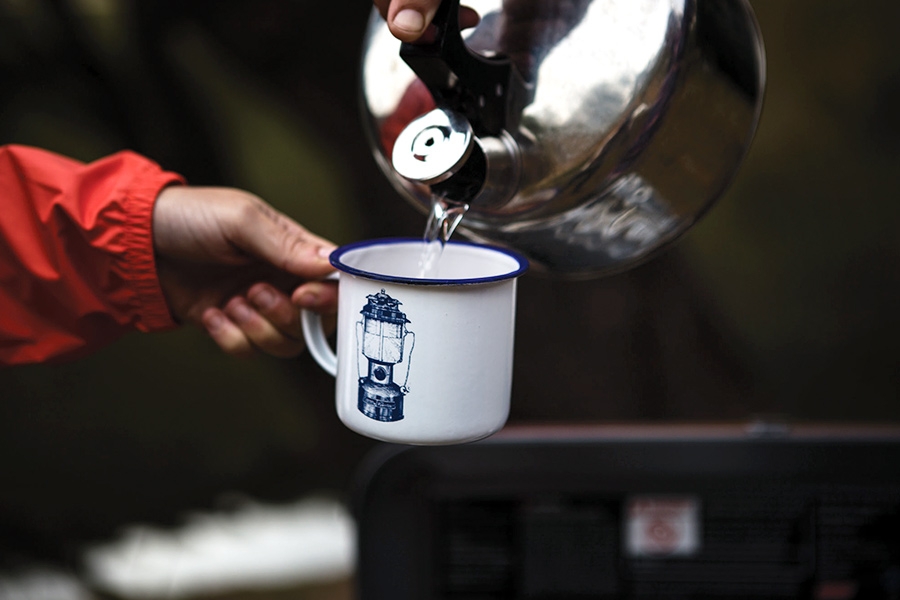 Pouring hot water from a kettle into an enamel camping mug
