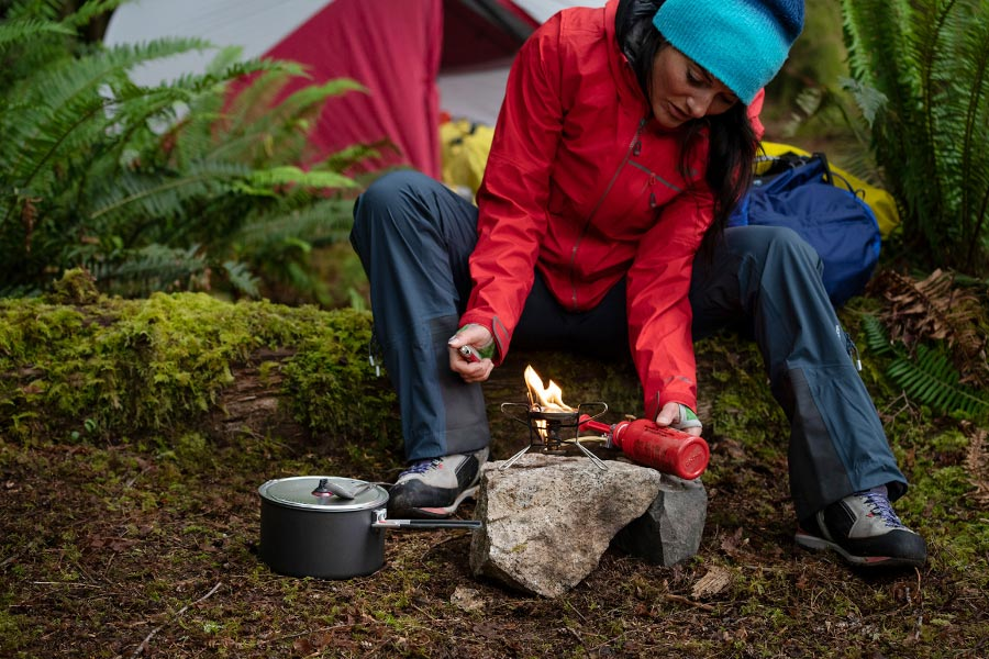 A woman lighting an MSR fuel stove in a forest campsite