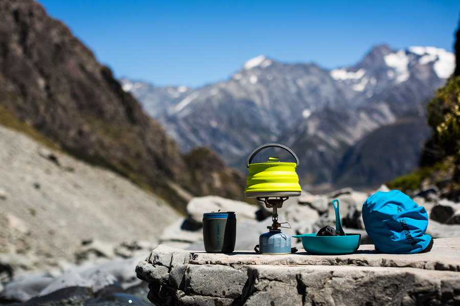 A Sea to Summit cookset on a flat rock with snow capped mountains in the background