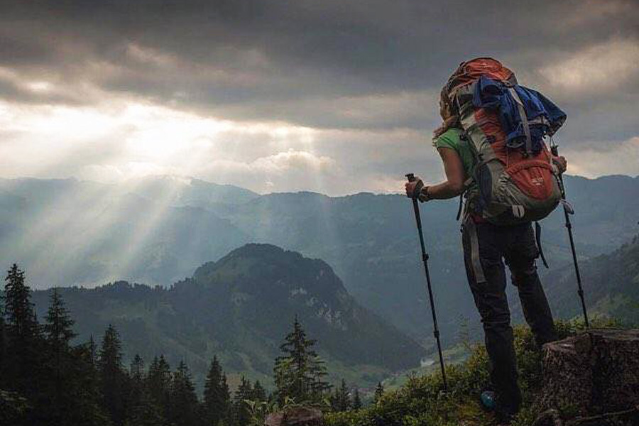 Woman looking out over mountain top with hiking poles