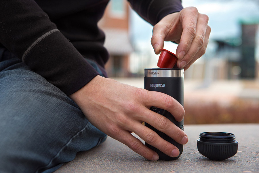 Man putting coffee into Wacaco Nanopresso while out and about