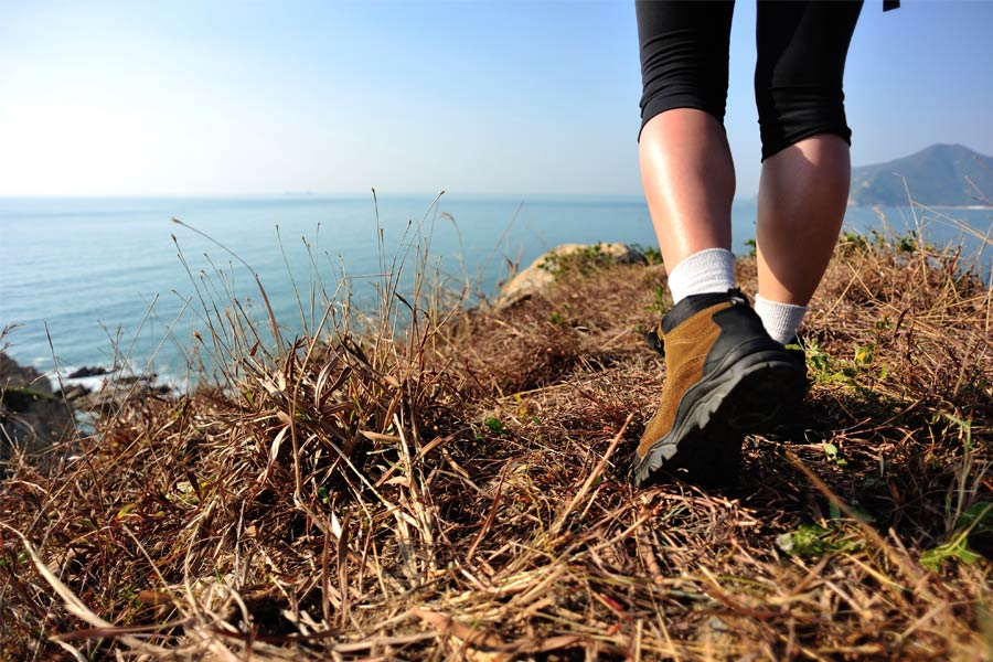 Woman wearing boots looking over sea cliff