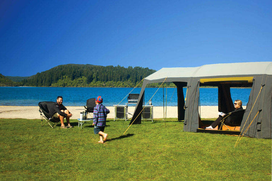 Family sitting on chairs next to their Zempire cabin tent outdoors