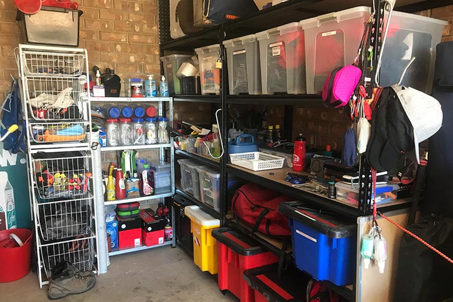 An organised garage lined with shelving filled with containers and camping supplies