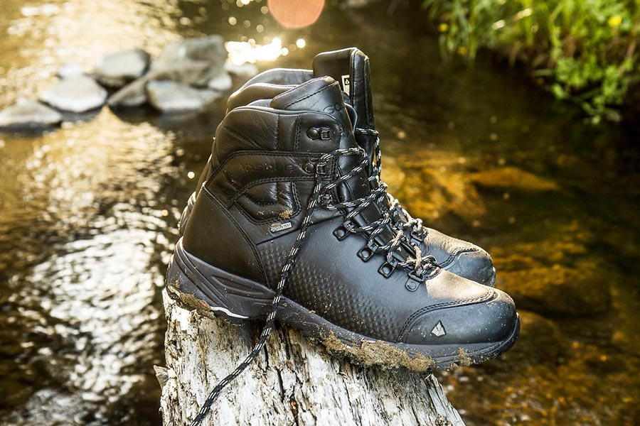 A pair of black, muddy Vasque boots sit on a log hanging over a creek