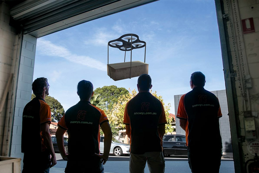 Men workers stare at the delivery drone flying at Snowys