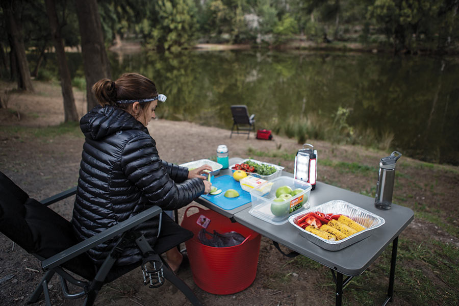 A woman preps food on a table next to a river