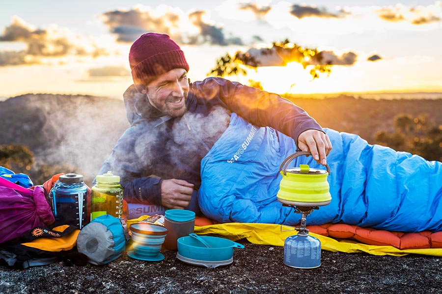A man lies outside in a sleeping bag, wearing a beanie and heating a kettle on a hiking stove