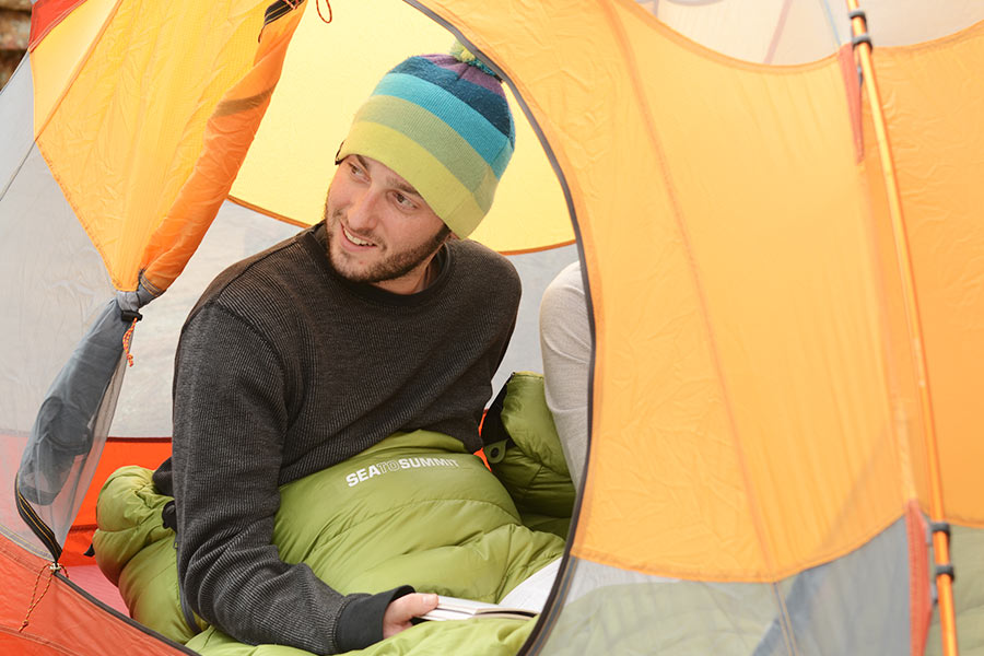 A man wearing a beanie and thermal top sits up in his sleeping bag inside a tent