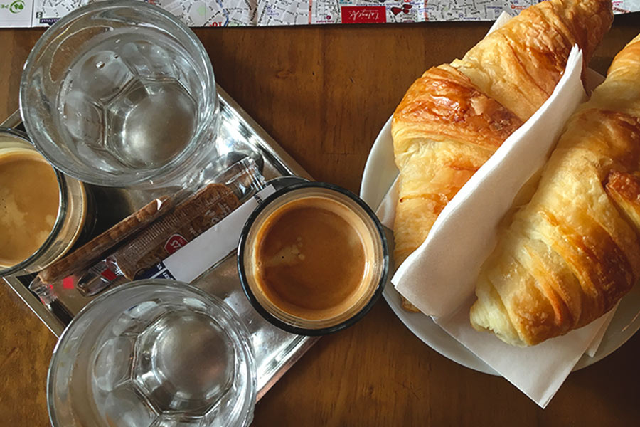 Parisian breakfast of black coffee and plain croissant