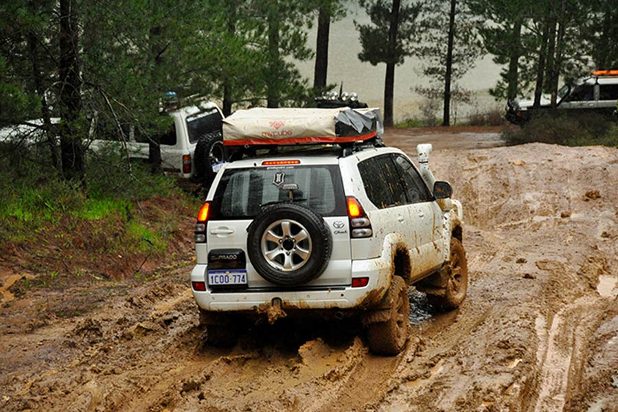 Toyota Prado climbing up a muddy hill in Australia
