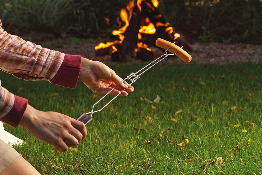 A person holding an extendable campfire fork in front of a fire, with a sausage on it ready to cook