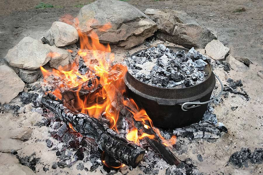 A camp oven, covered in hot coals, sits on a fire