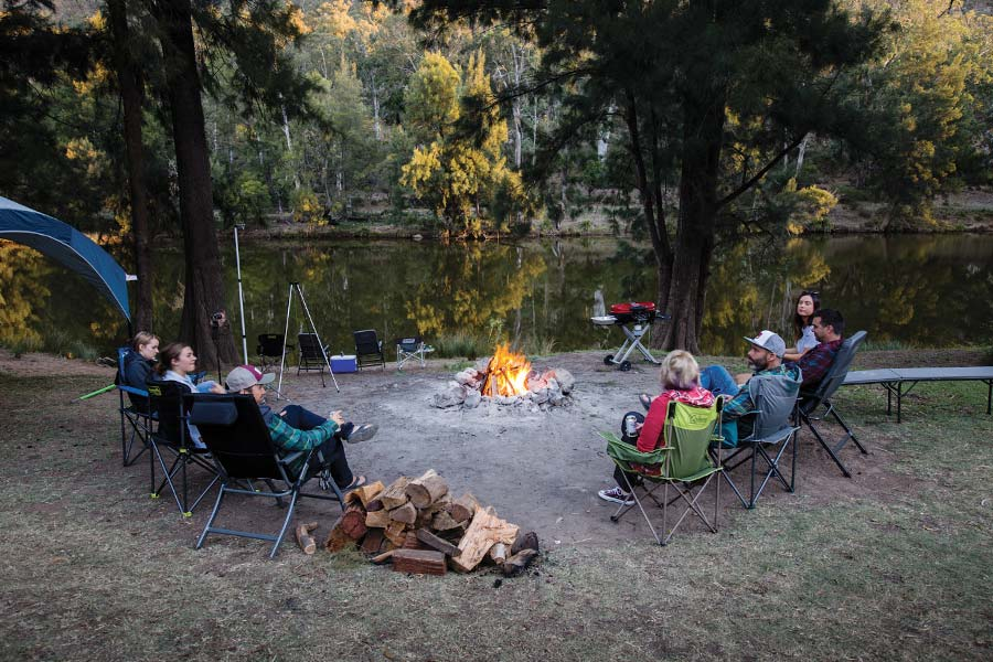 People sit in chairs around a campfire, on a clear riverbank