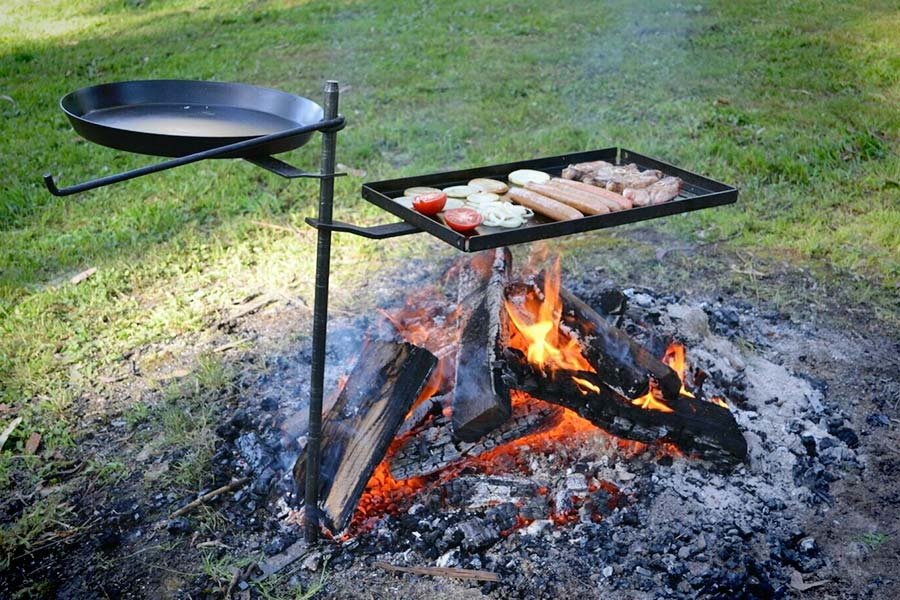 A cook stand next to a fire, holding a hotplate filled with sausages, onion and tomatoes