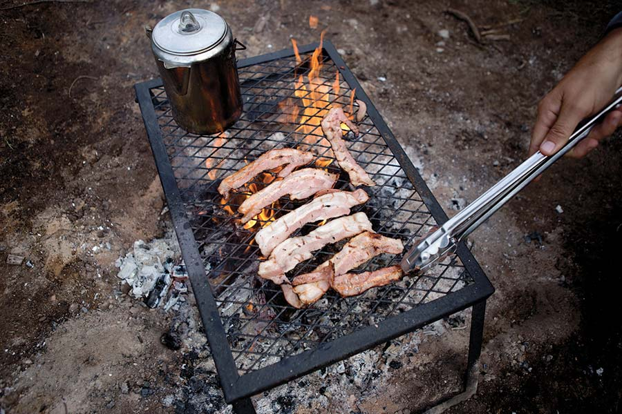 Bacon cooks on a grill that sits over a camp fire