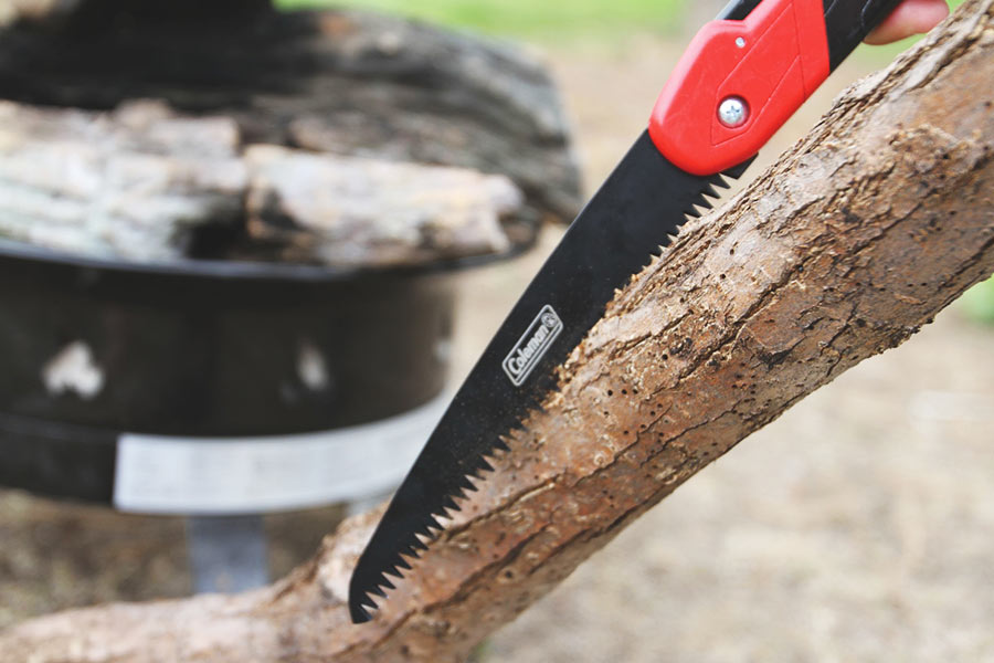A tree branch is cut with a small saw