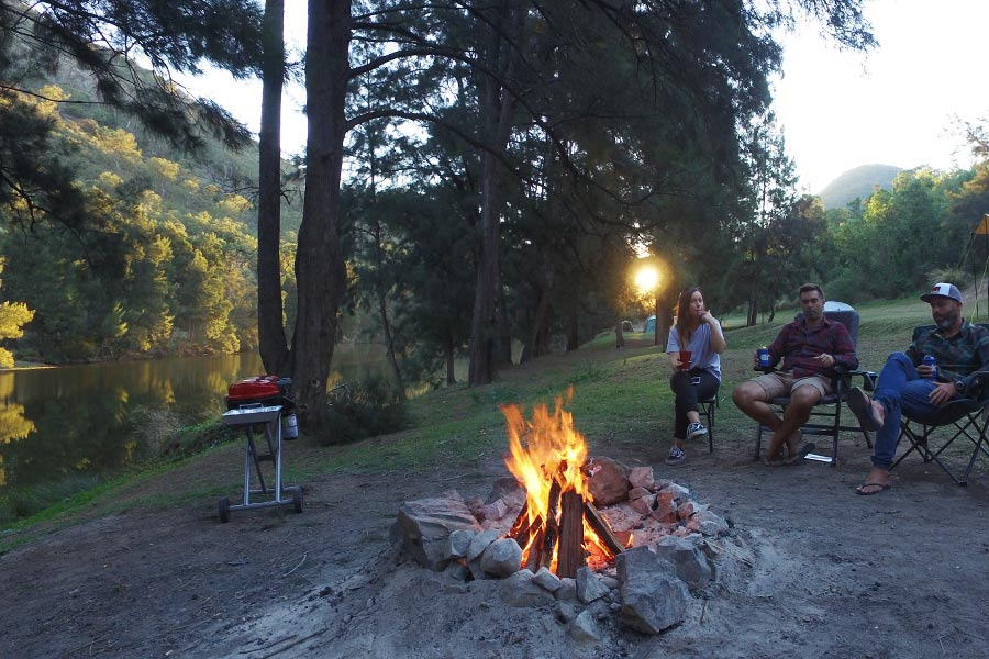 A few people sit in chairs on a riverbank, around a campfire