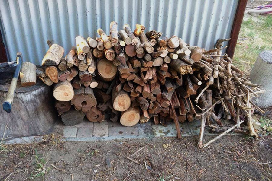 Chopped up pieces of wood against corrugated iron wall.