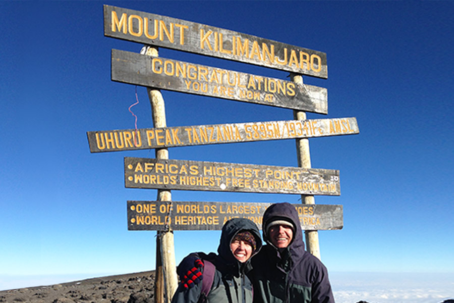 Posing next to the Mt. Kilimanjaro summit sign
