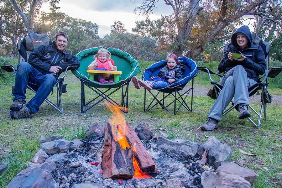 Family with two young girls eating around the campfire