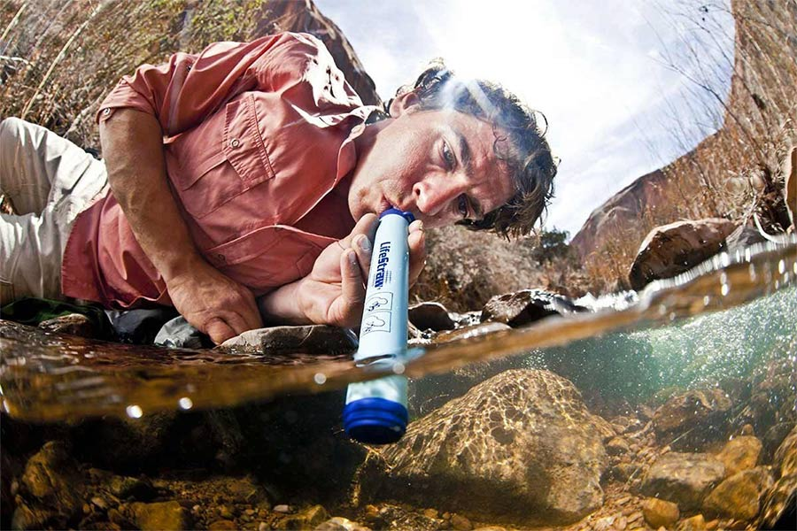 Using a Lifestraw to drink water from a river