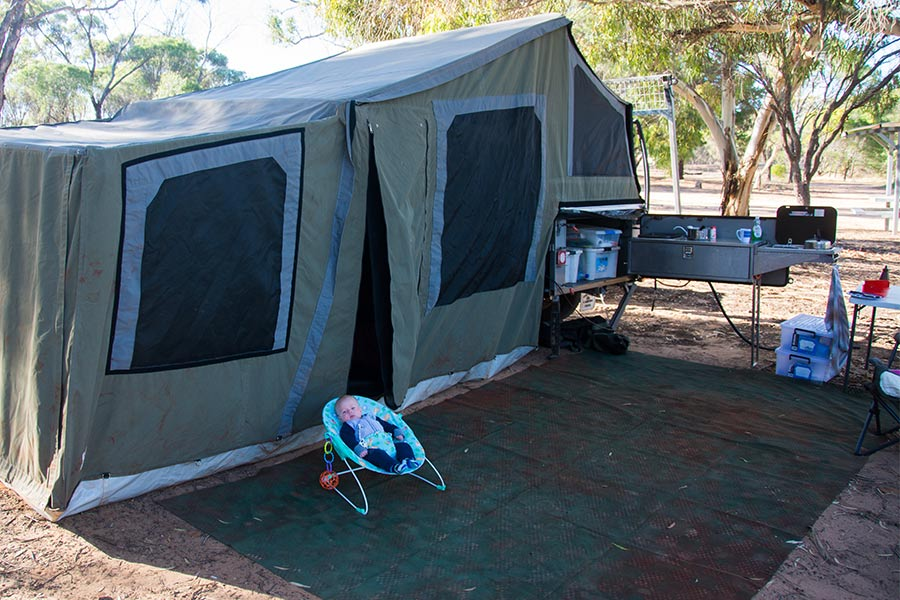 Baby sitting next to tent