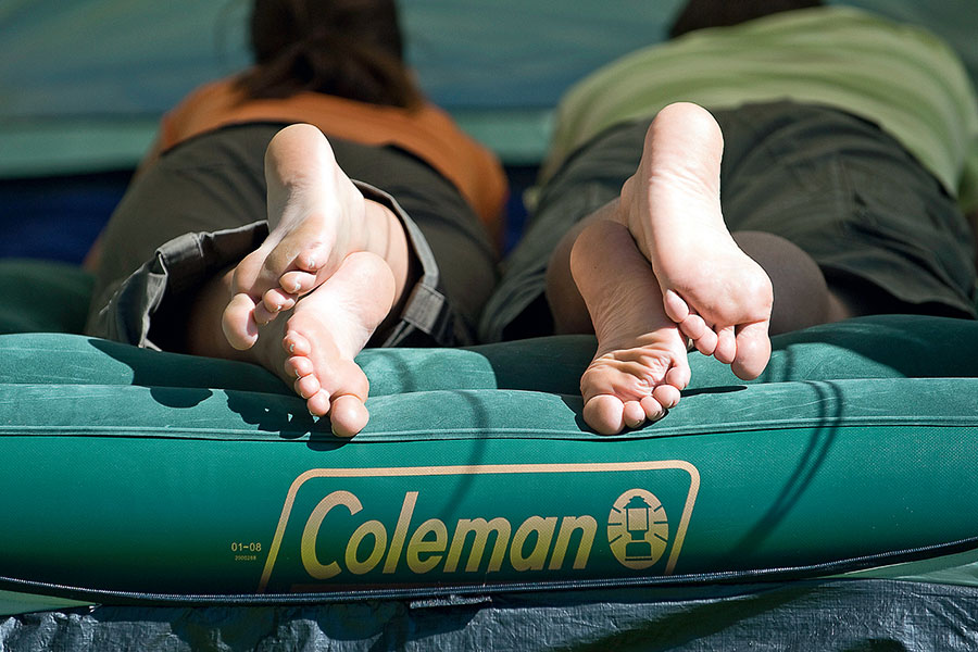Man and woman lying on Coleman mattress in tent