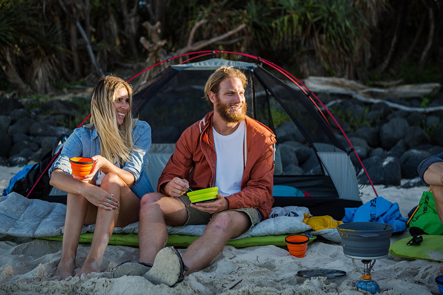 A couple sit on their mattress on the sand outside their tent, eating a cooked breakfast