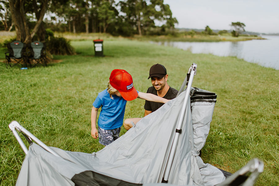 A father and son wearing caps while they pitch a tent