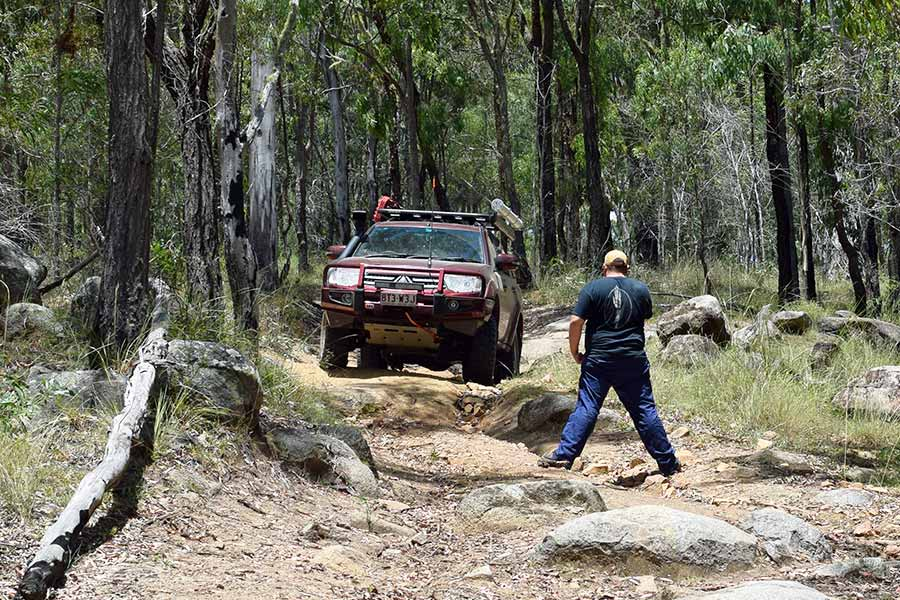 Man spotting 4WD to help guide 4WD in rough terrain