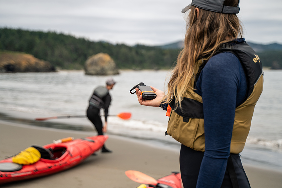 Two kayakers - one stands in the foreground holding a SPOT Satellite Messenger and the other is in the background pulling his kayak near the shore.