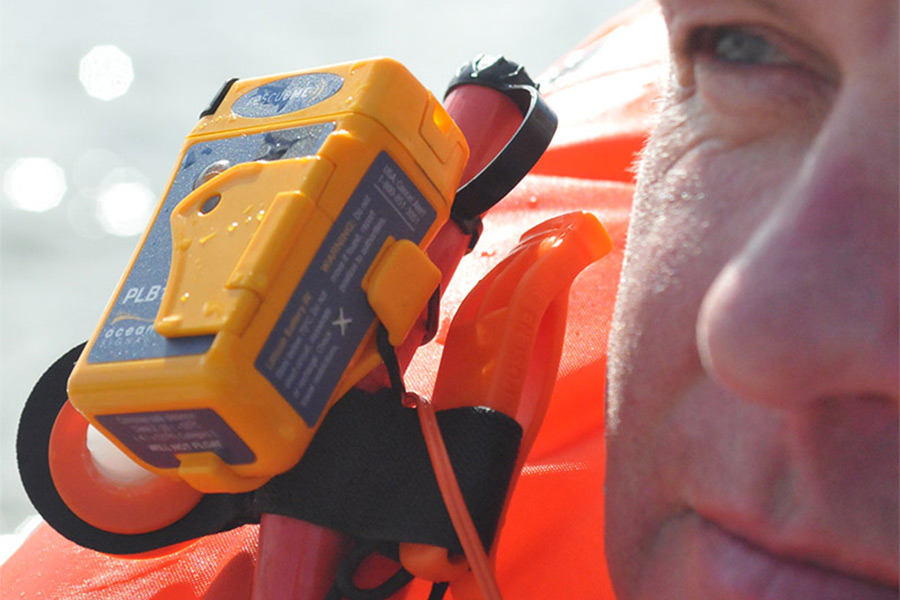 Close up of the Ocean Signal RescueMe PLB1 attached to a life vest. The side of a man's face takes up the right of frame.