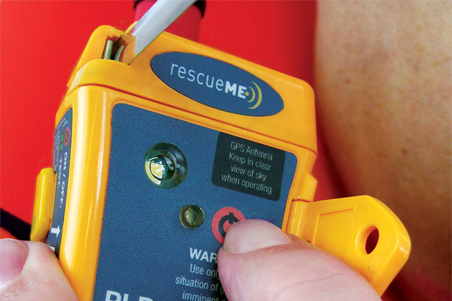 Extreme close up of a thumb hovering over the SOS button on the RescueMe PLB1.