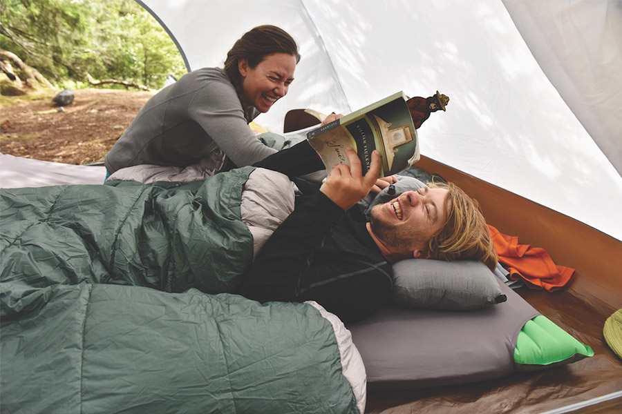 Couple lying on camping mat with a sheet liner