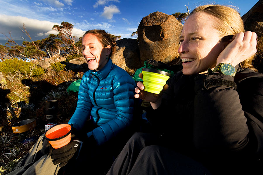Two women sitting outdoors drinking from S2S cups