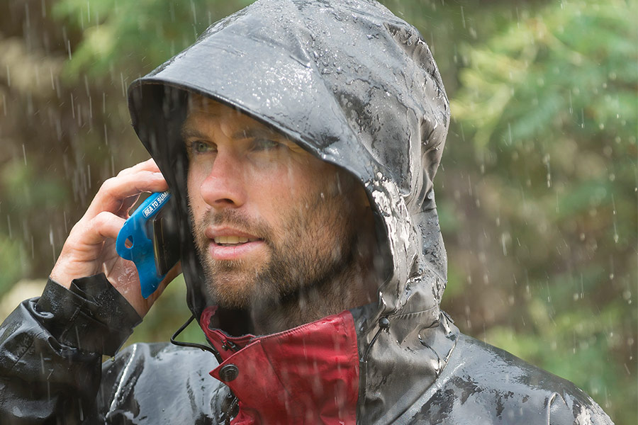 Man holding phone in waterproof case whilst it rains