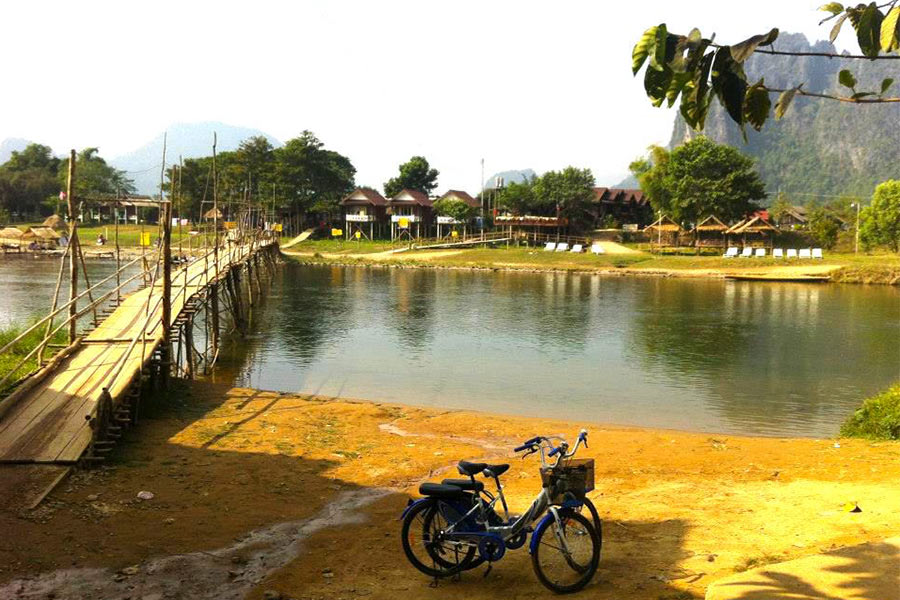 Bikes by the bridge and river in Laos