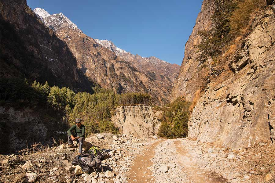 Taking a break from carrying a heavy pack on the Annapurna circuit