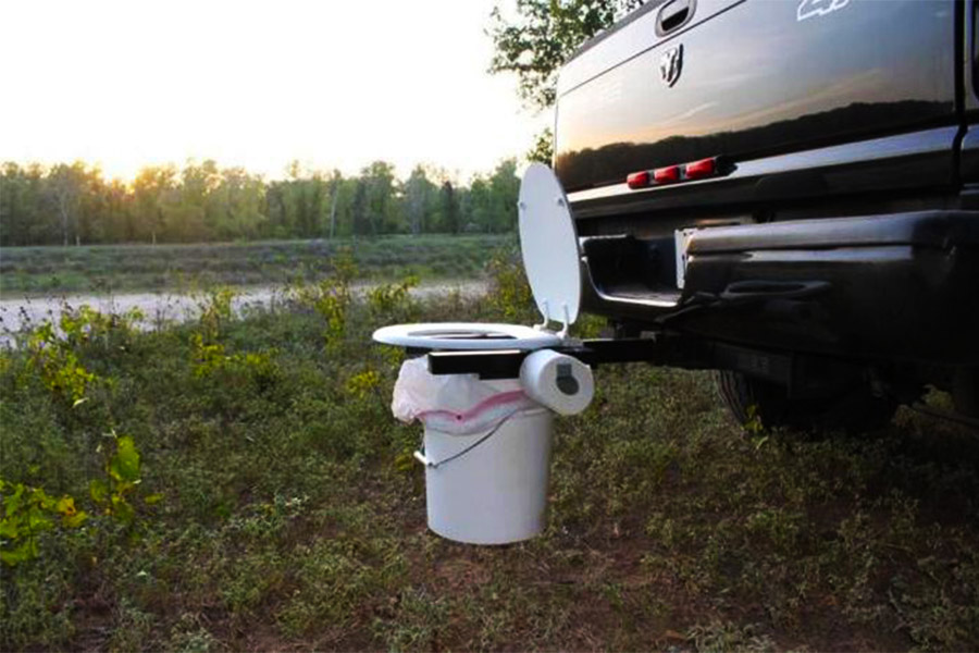 Portable toilet positioned on the bumper of a car