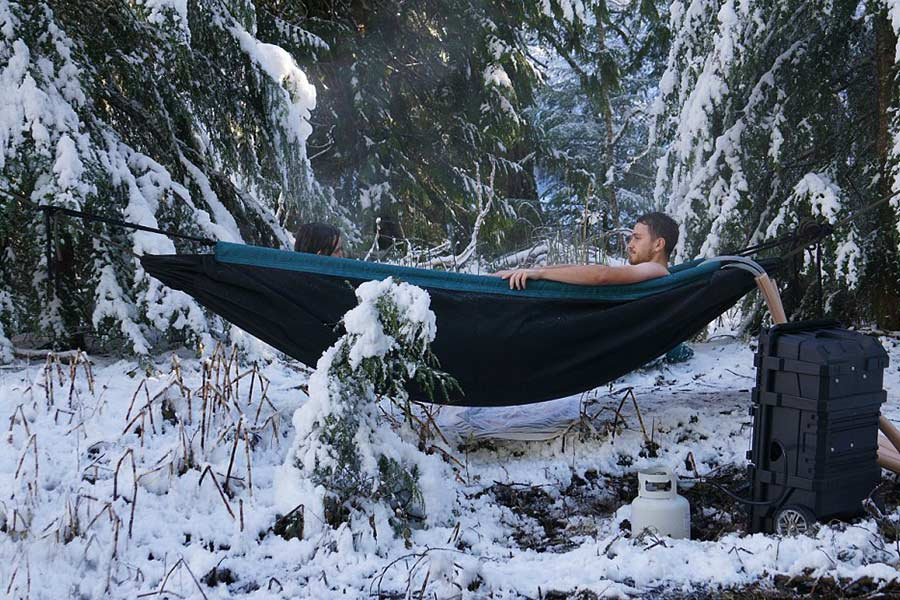 Couple lying in a Hydro Hammock in snow covered forest