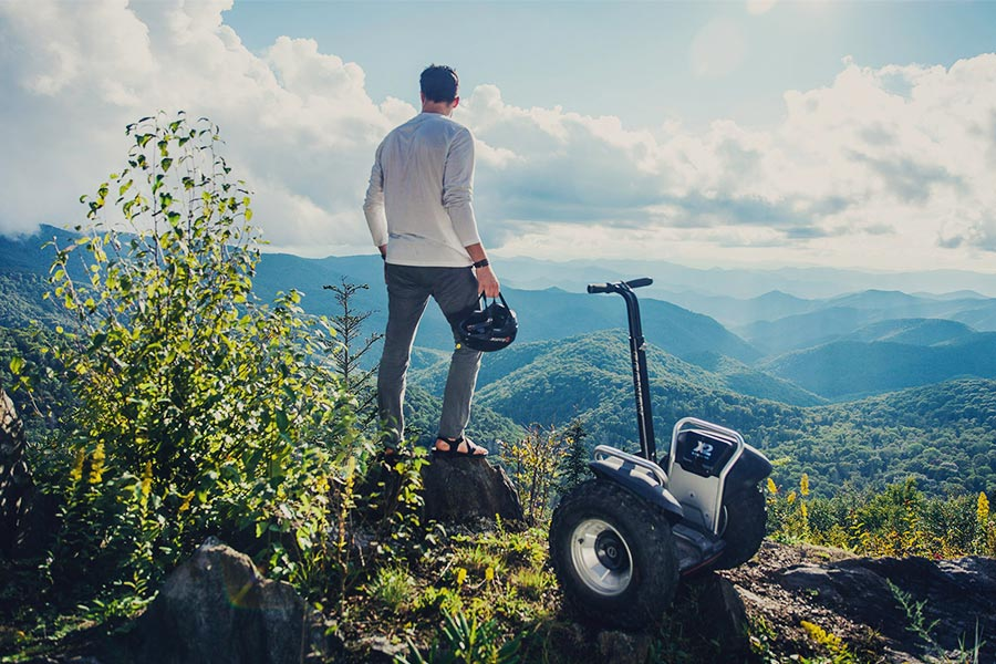 Man looking at view with a Segway x2 SE parked next to him
