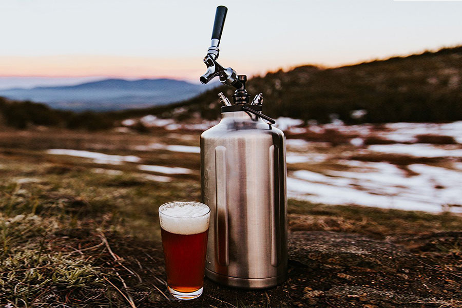 Glass of beer outdoors with Trail Keg next to it