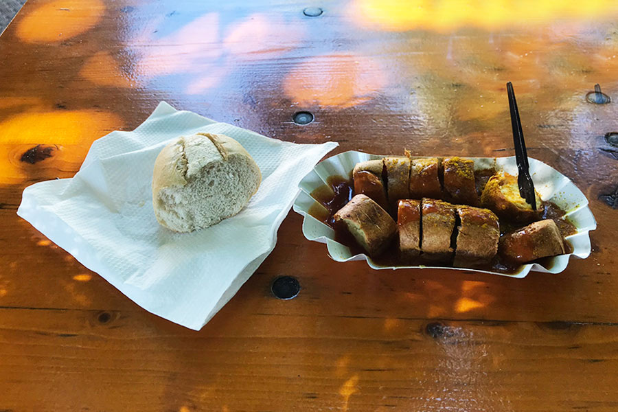 The fast food dish of Currywurst next to a piece of bread