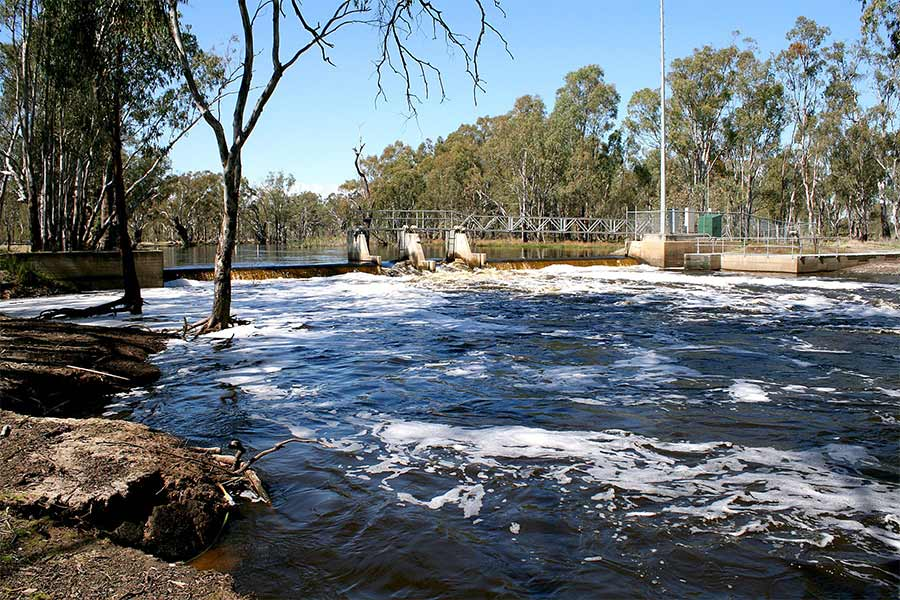 Black water flowing over a weir near Barmah