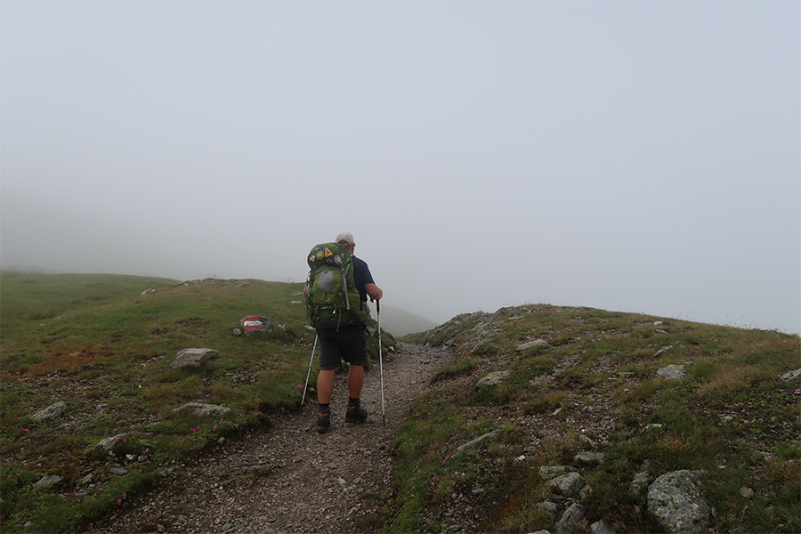 Man hiking with rucksack in heavy mist