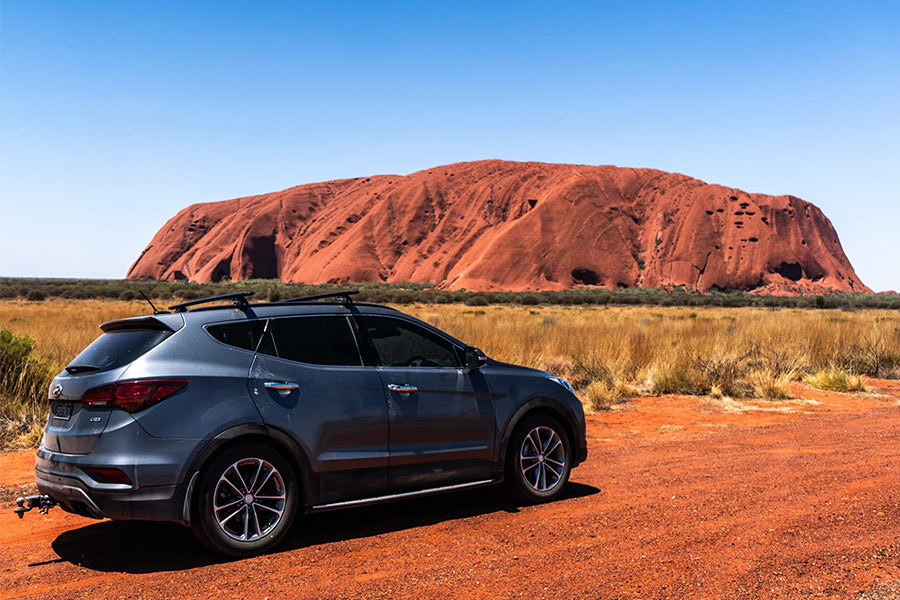 View of vehicle with Uluru in the background