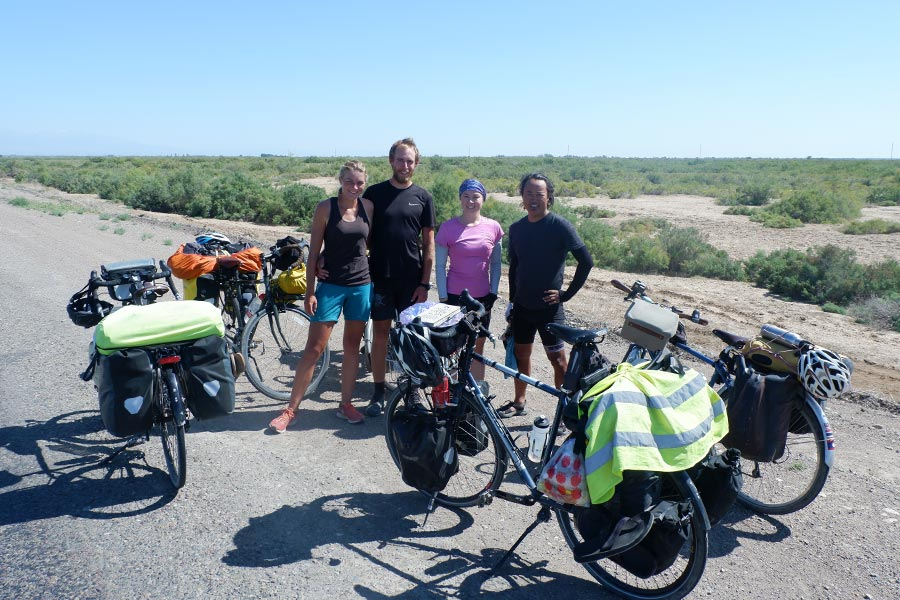 Group of four people posing with their bikes along a road in Kazahkstan